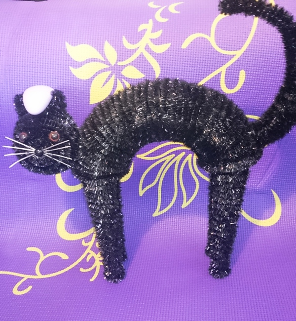 A halloween cat decoration with a lelo toy on it.